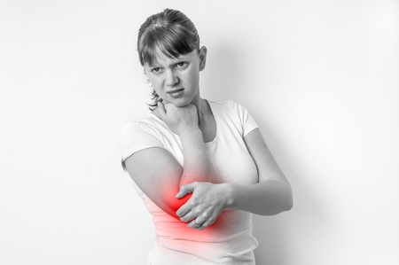 Woman with elbow pain is holding her aching arm - black and white photo
