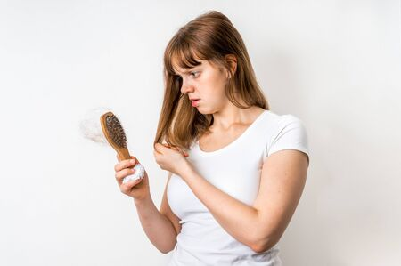 Woman with hairbrush is suffering from hair loss