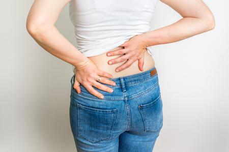 Vrouw met rugpijn die haar pijnlijke rug houdt - lichaamspijn