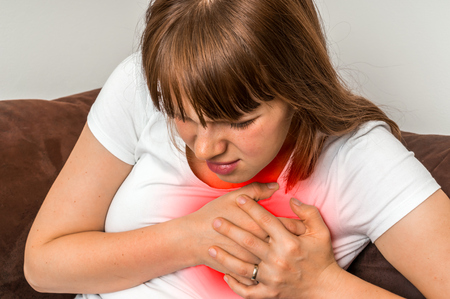heartattack: Woman on sofa having heart attack - chest pain