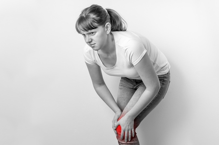 Woman with knee pain is holding her aching leg - black and white photo