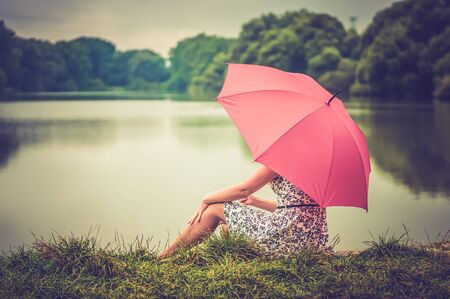 Young beautiful woman with red umbrella sitting near the pond and looking far away distance - retro and vintage style