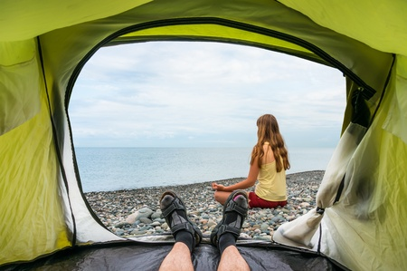 View from inside a tent on the young lady practicing yoga at seashore in summer Stock Photo