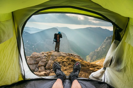 View from inside a tent on the young man on a rock and beautiful mountains in Macedonia
