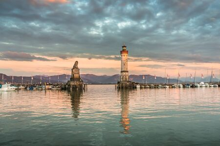 Evening seascape with lighthouse in harbor of Lindau in lake Constance, Germany Stock Photo