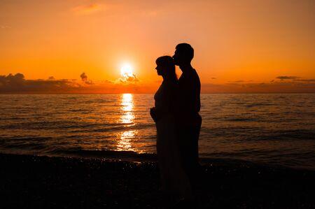 Romantic scene of love couples partners at sunset near sea Stock Photo