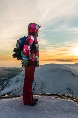 Girl watching at the sunset on the top of mountain Snezka in the Czech Republic Stock Photo