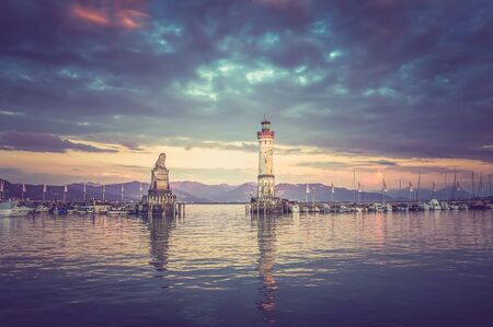 Beautiful evening seascape with lighthouse in harbor of Lindau in lake Constance, Germany - retro and vintage style