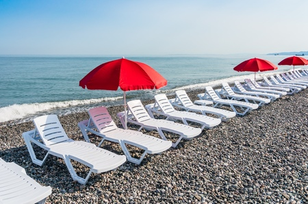 Beach chairs or beds and sun red umbrellas on the beach near sea