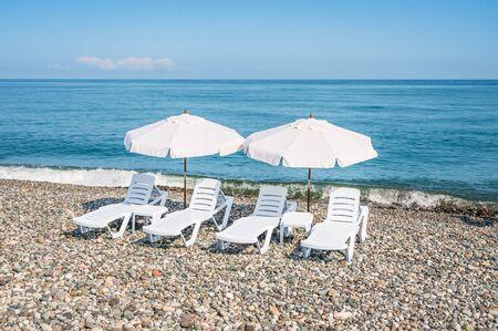 Four white plastic beach chairs and two white parasols on the beach near sea Stock Photo