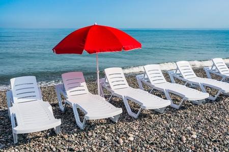 Sunbathing plastic beds and red umbrella on the beach near sea Stock Photo
