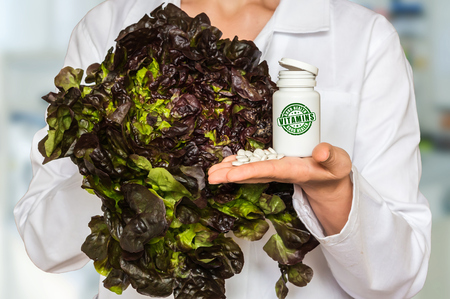 prophylaxis: Young doctor holding fresh lettuce and bottle of pills with vitamins and compare them Stock Photo