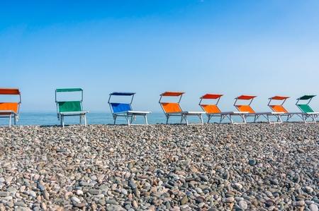 Colorful beach chairs on the shingle beach near sea Stock Photo
