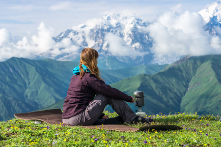 Young lady hiker preparing something to eat in the mountains, Georgia (Svaneti) Stock Photo