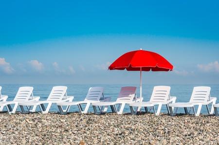 Sun umbrella and beach beds on the shingle beach near sea Stock Photo