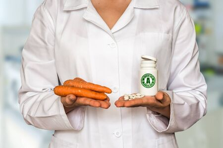Young doctor holding fresh carrots and bottle of pills with vitamin A and compare them