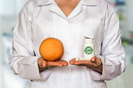Young doctor holding fresh grapefruit and bottle of pills with vitamins and compare them