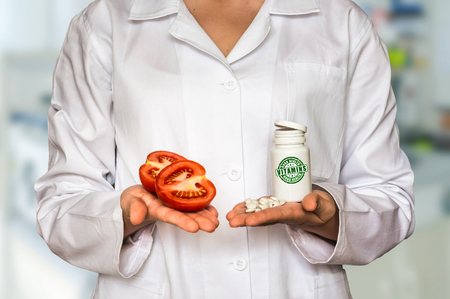 Young doctor holding fresh tomato and bottle of pills with vitamins and compare them