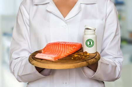 Young doctor holding salmon on a wooden plate and bottle of pills with fish oil (Omega-3) and compare them Stock Photo