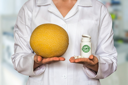 Young doctor holding fresh yellow melon and bottle of pills with vitamins and compare them