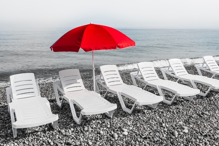 Red sun umbrella and plastic beach beds, black and white concept Stock Photo