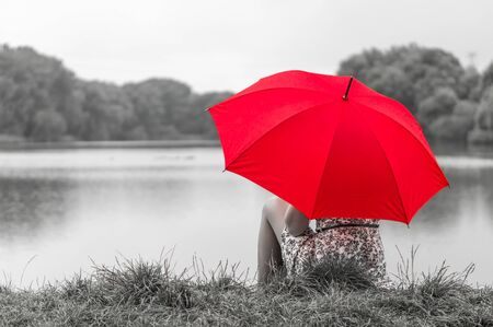 Beautiful girl with red umbrella near the pond
