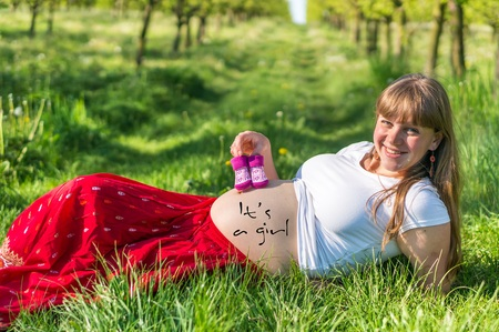 Pregnant young girl lying on the grass in the fruit garden
