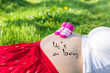 Pregnant young girl on the grass in the garden with inscription: Its a boy on her belly Stock Photo