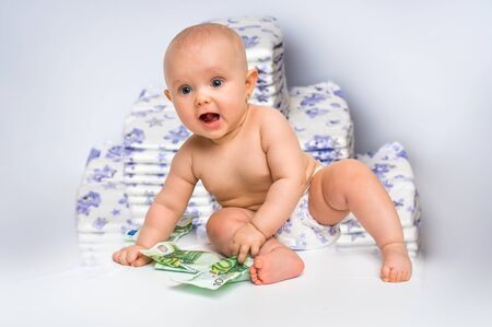 Cute baby with money isolated on blurry diapers background - expensive childcare