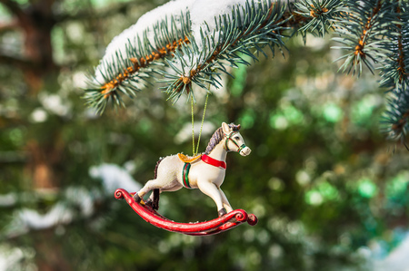 Rocking horse, closeup of Christmas tree decoration on snowy pine branch Stock Photo