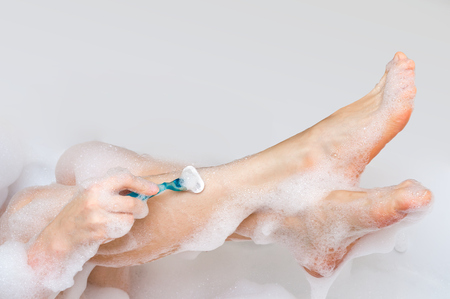 Woman shaving legs with razor in bathroom at home