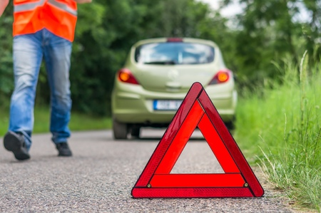Broken car on the road and unhappy driver with red warning triangle Stock Photo