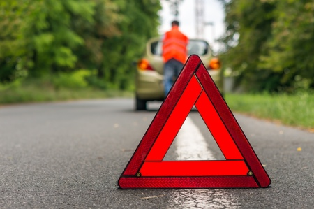 Unhappy driver and broken car on the road. Red warning triangle. Stock Photo