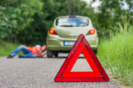 pushes: Driver lying under the broken car and warning triangle Stock Photo