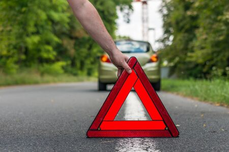 pushes: Driver putting out a traffic warning sign - broken car on the road