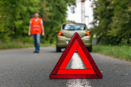 Broken car on the road and red warning triangle Stock Photo