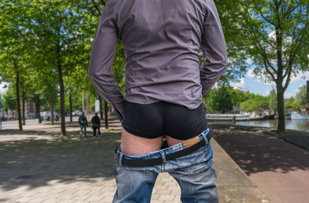 urination: Standing man peeing to a street in big town - incontinence concept