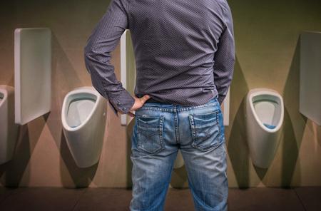 pene: Permanente peeing hombre a un urinario en el baño o el concepto de incontinencia