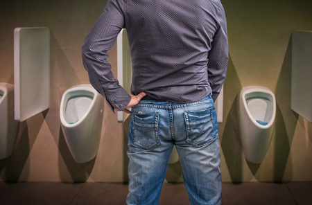 Standing man peeing to a urinal in restroom or incontinence concept