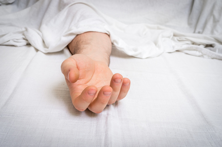 The dead man's body under white cloth with focus on hand in a morgue 版權商用圖片