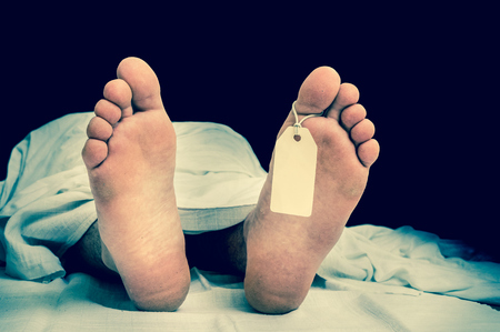 toe tag: The dead mans body with blank tag on feet under white cloth in a morgue - retro style Stock Photo