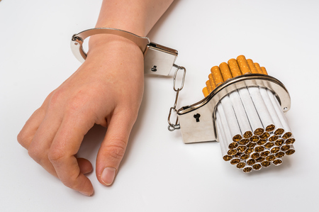 Female hand with handcuffs and cigarettes on white background - concept of smoking dependence