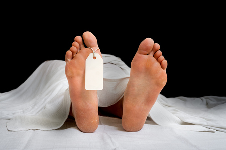 The dead womans body with blank tag on feet under white cloth in a morgue