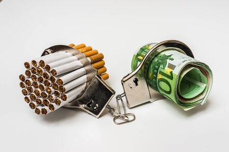 Cigarettes and money with handcuffs as a concept of smoking cost Stock Photo