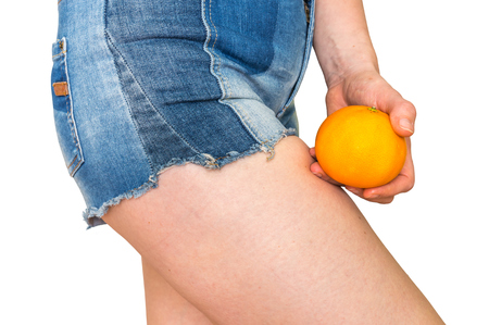 Beautiful woman with fresh orange isolated on white - cellulite concept. Stock Photo