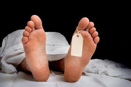 The dead mans body with blank tag on feet under white cloth in a morgue Stock Photo