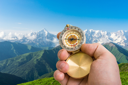 Traveler man with compass seeking a right way in the mountains in Georgia - navigation concept
