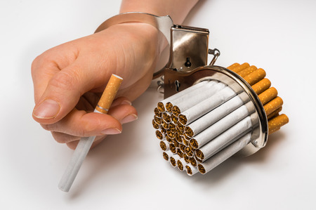 narcotic: Female hand with handcuffs and cigarettes on white background - concept of smoking dependence