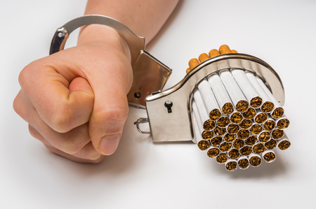 cuff: Female hand with handcuffs and cigarettes on white background - concept of smoking dependence