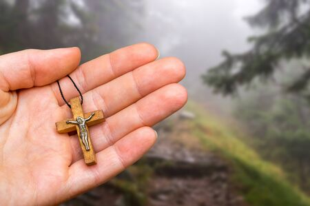 Female hand with wooden cross on haunted forest background - religion concept Stock Photo